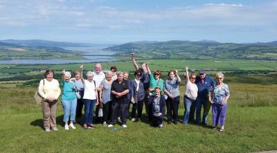 A Gathering in Donegal: Kerryman Mark Lyons, the bus driver assigned to Cardinal O'Malley's pilgrimage tour to Knock last month, made this photo in Donegal at Grainan of Aileach ring fort overlooking Lough Swilly. Waving hello are pilgrims from New England who traveled through the Great Atlantic Way in Ireland's northwest while on the island for the services at Knock.